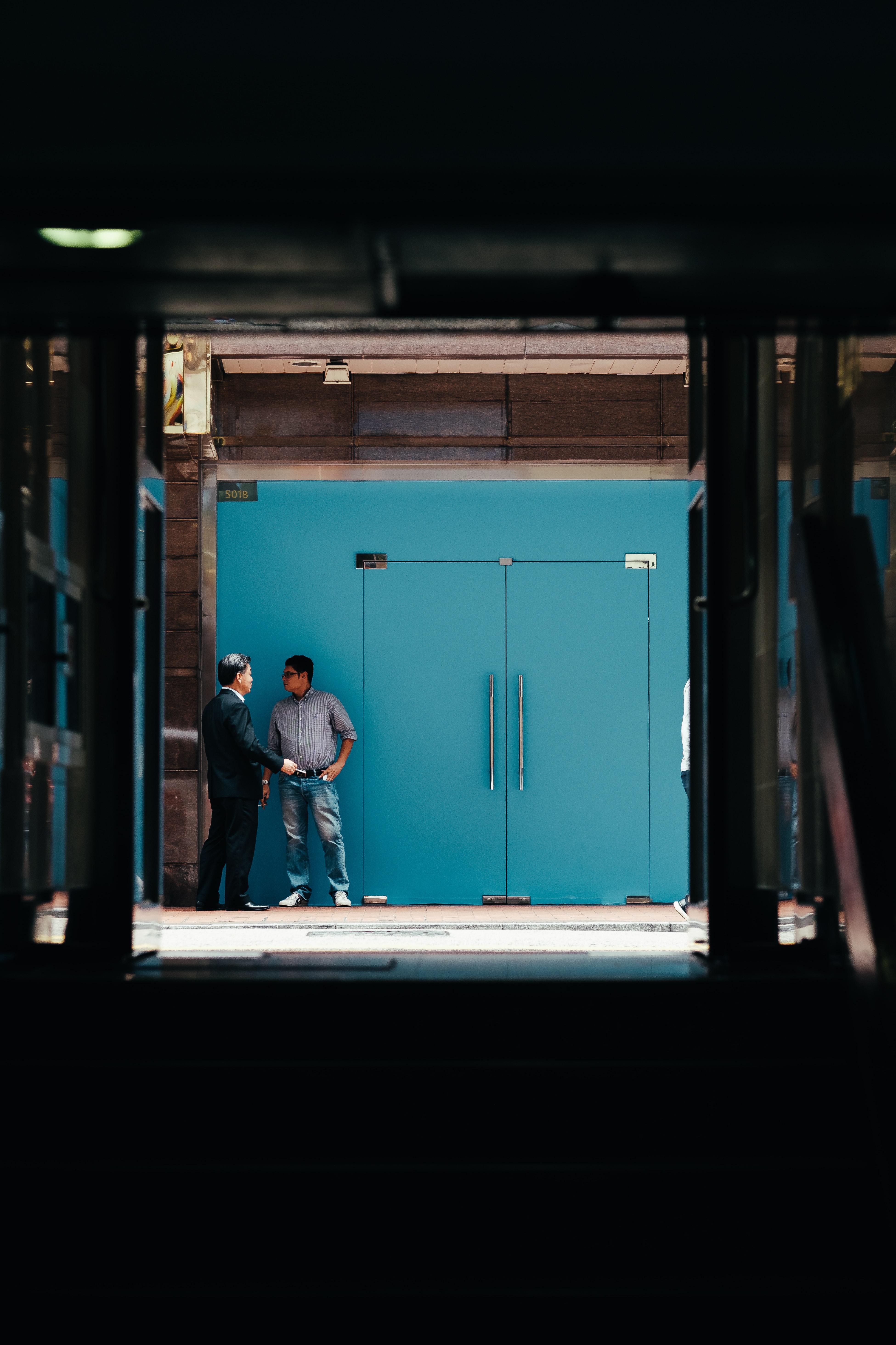 two men standing beside teal wooden doors
