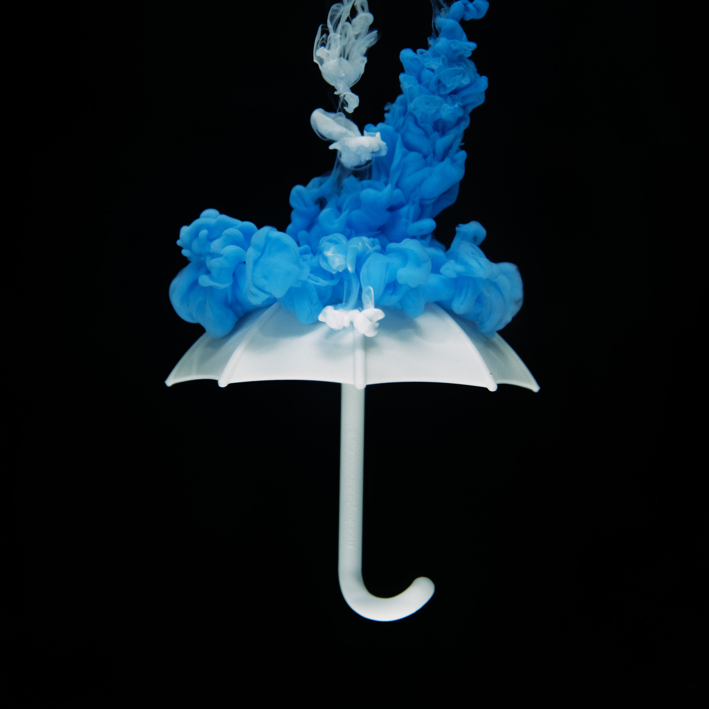 white umbrella with blue smoke against black background