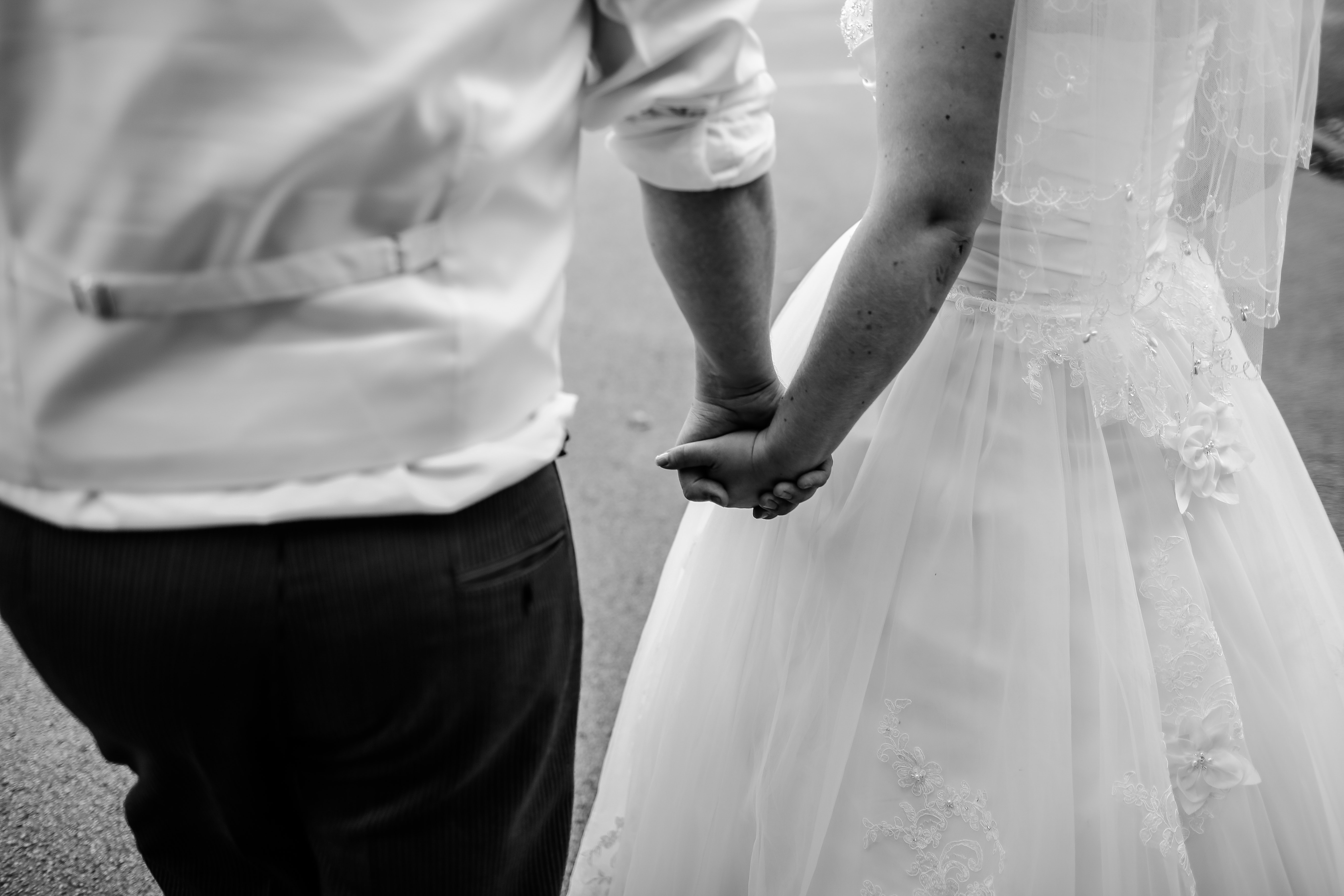 grayscale photo of wedded couple holding hands