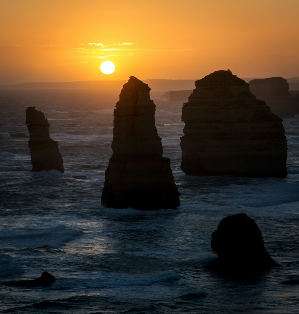 photograph of rock formation on sea during golden hour