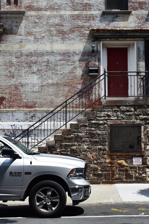 silver Dodge Ram 1500 near brown brick wall