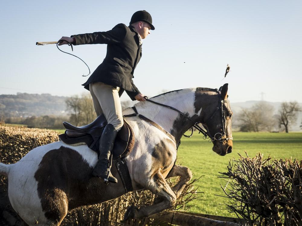 昼間に工場の近くで馬に乗る男