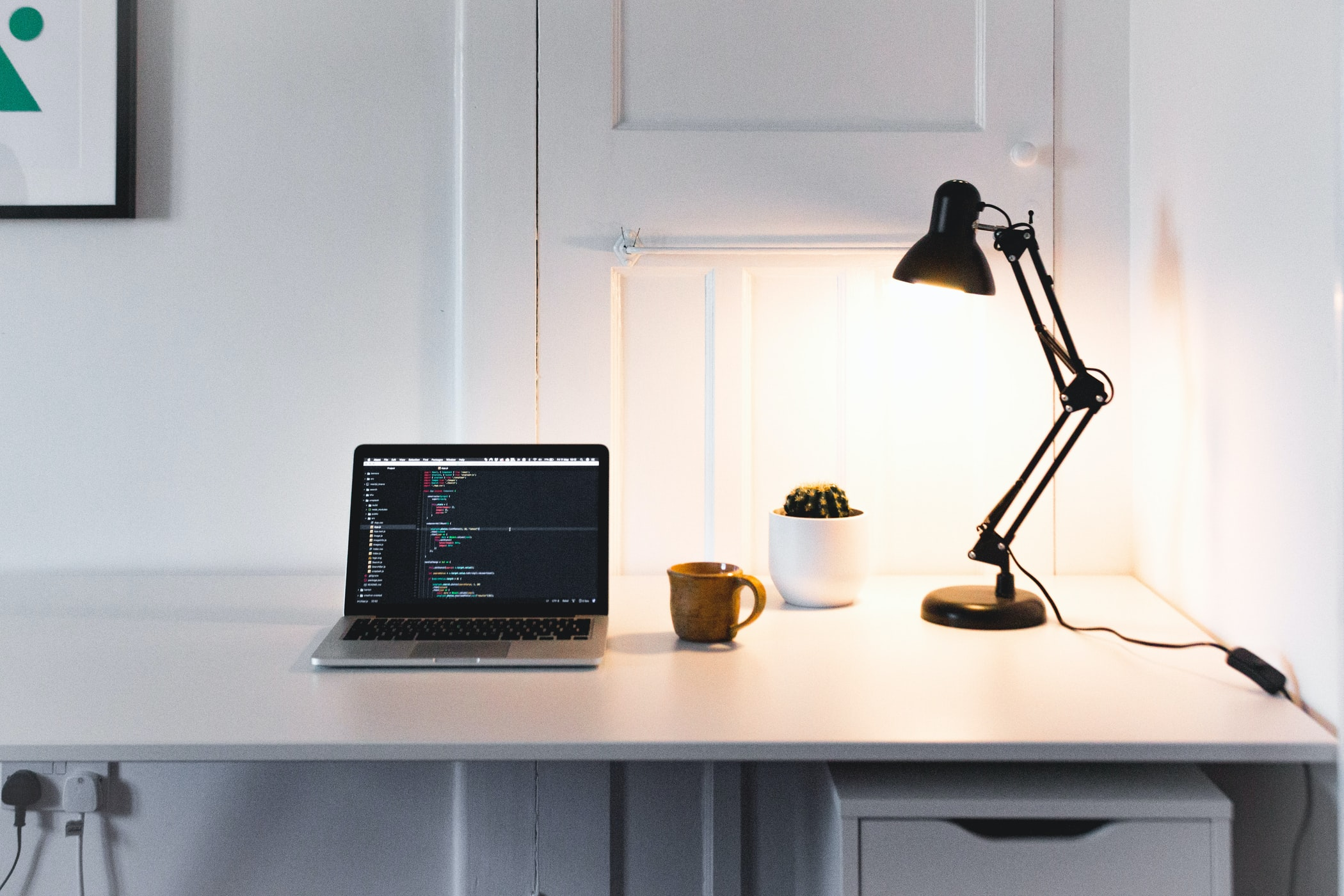 Laptop on top of a white desk, with code on the screen, next to an orange mug, a cactus and a black lamp.