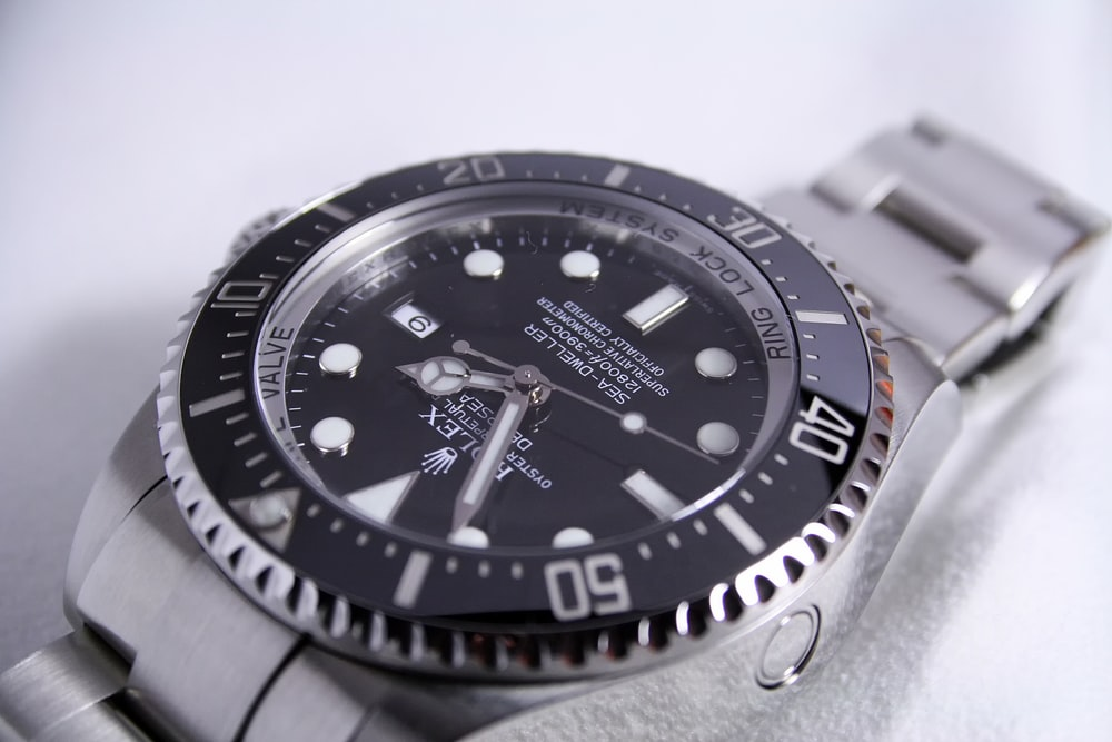 silver-colored Rolex analog watch reading at 1:55
