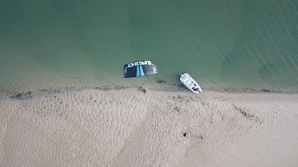 top-view of white boat docked on shore