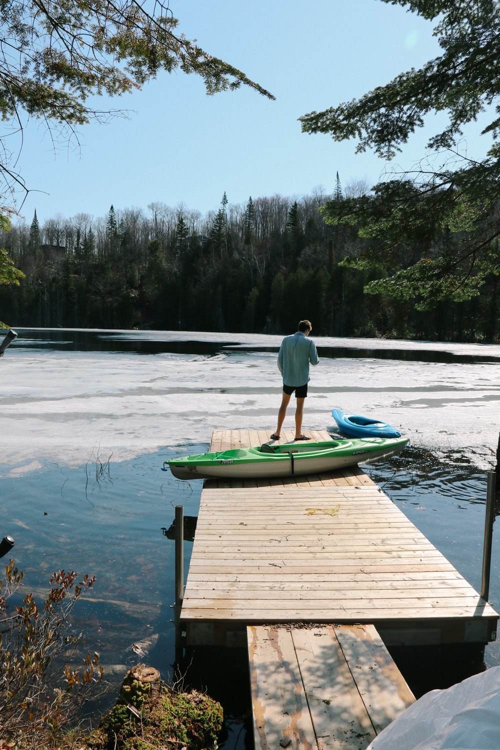 person standing on dock near kayaks