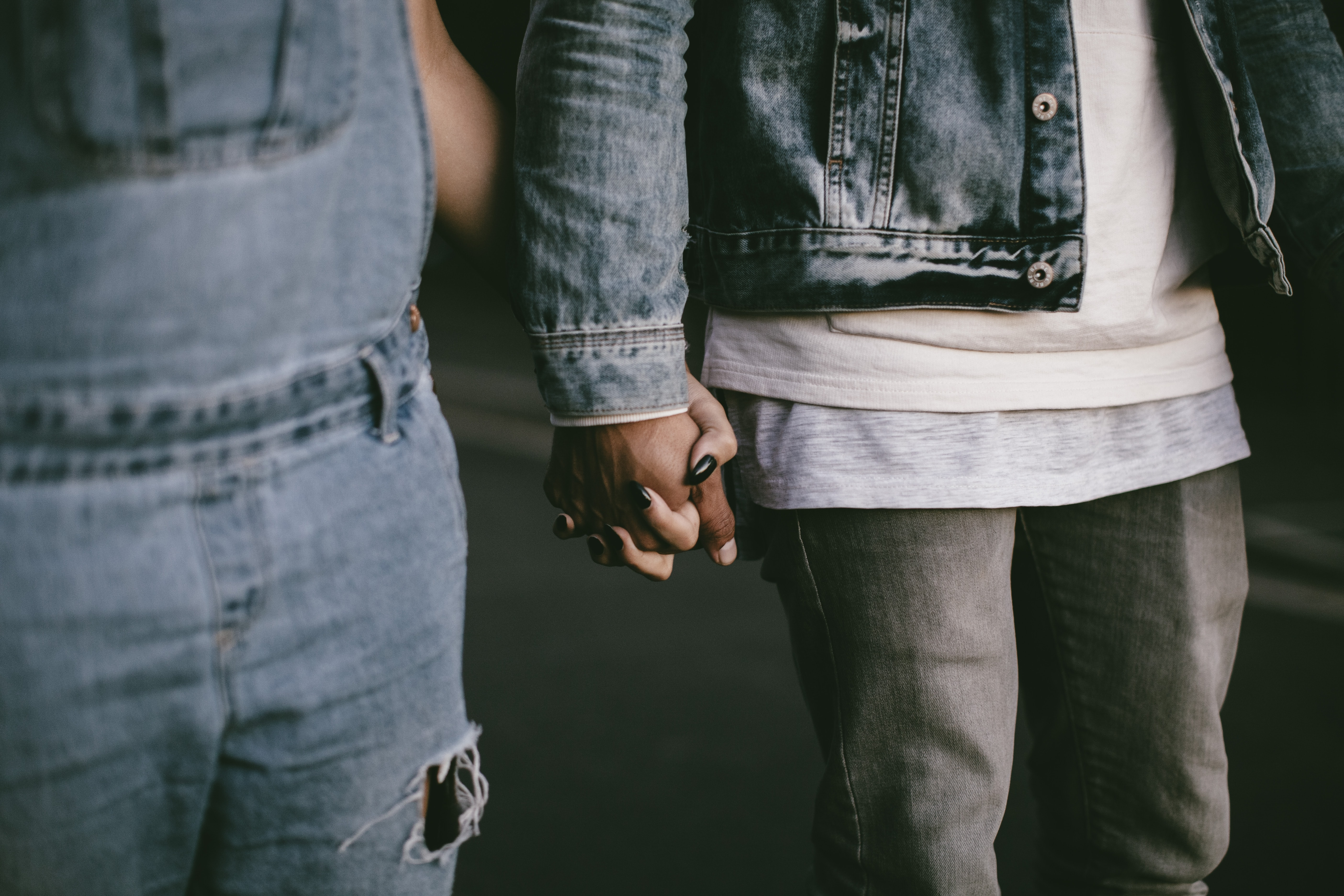 two person holding hands while walking