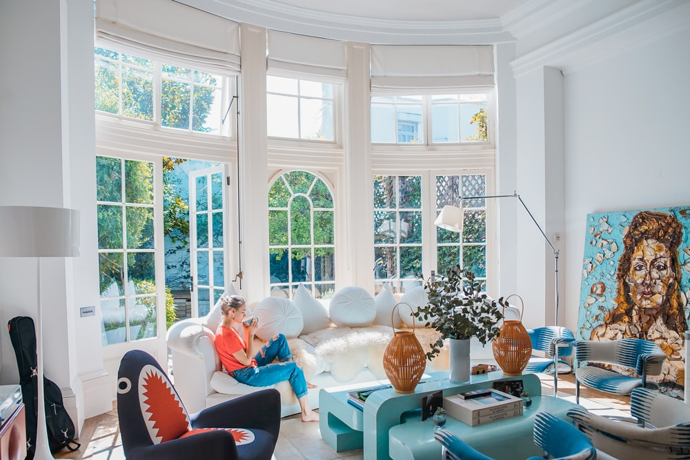woman sitting on white couch near window