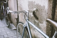 gray road bicycle leaning on gray wall