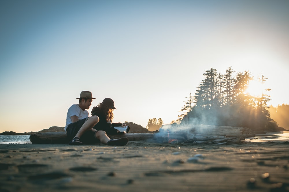 man and woman near bonfire