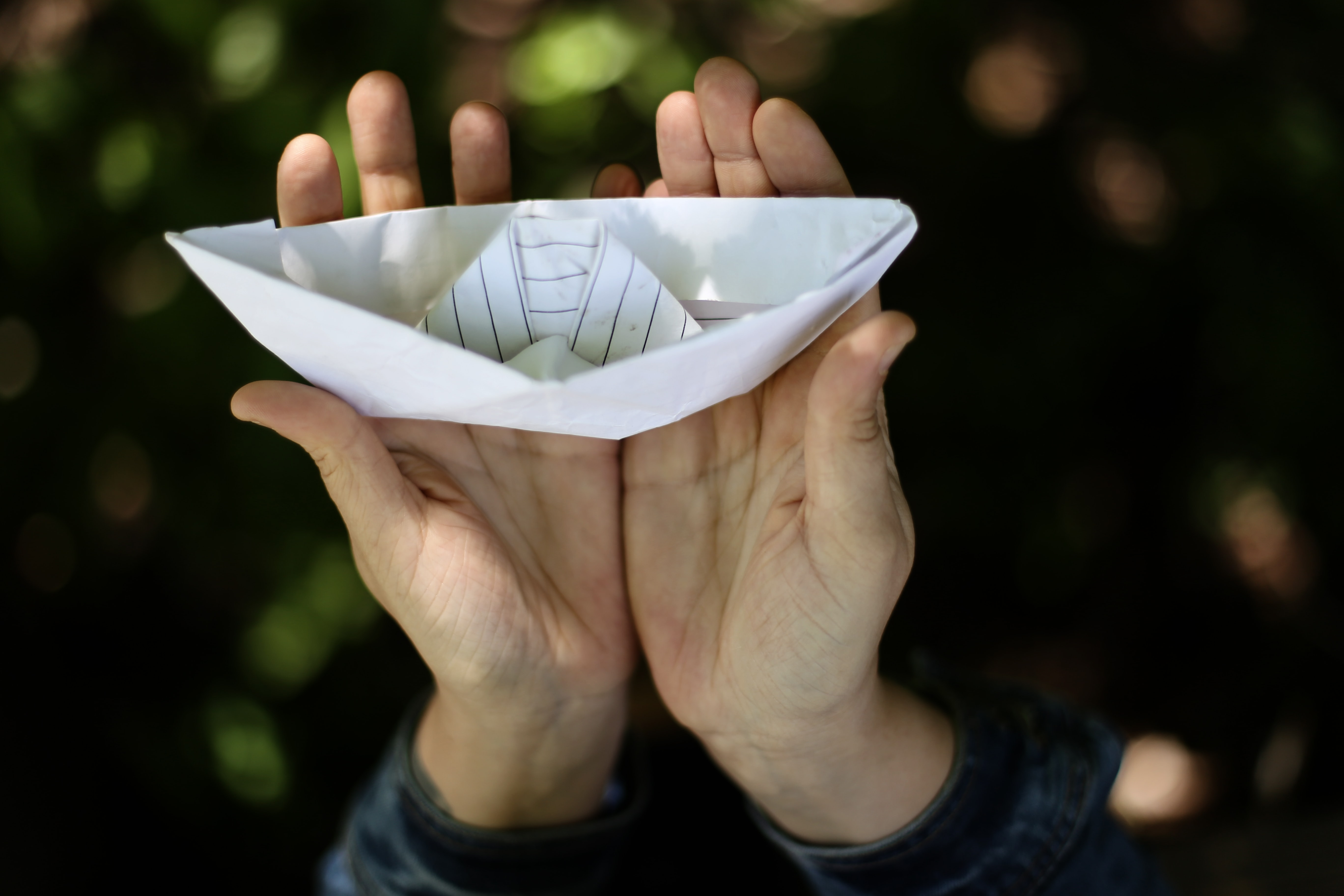 person holding paper boat in focus photography