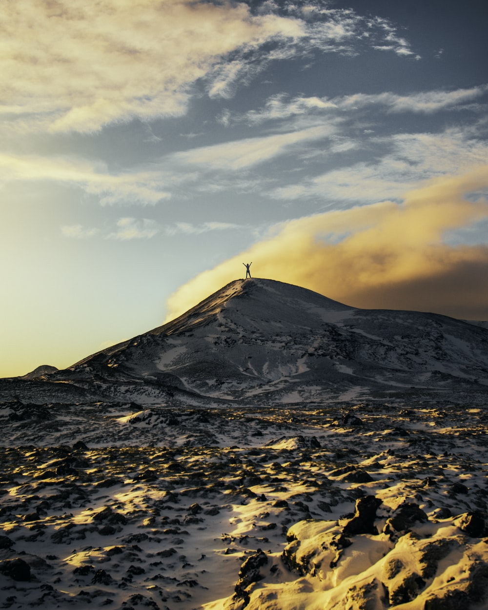 person standing on top of snow capped mountain during daytime
