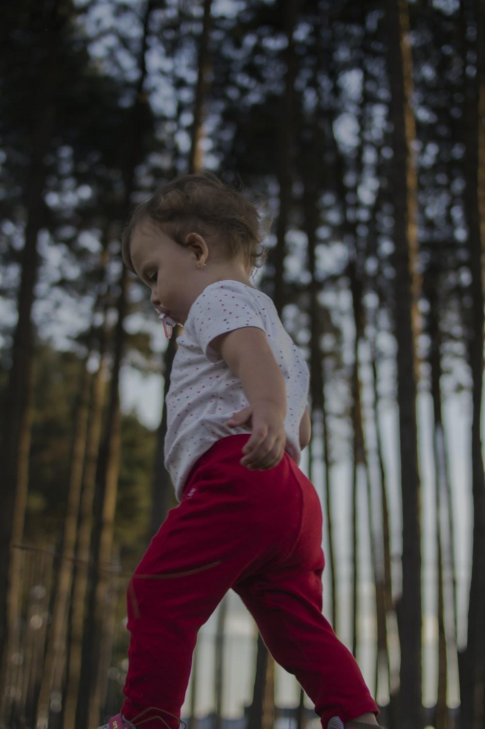 toddler walking near trees during daytime