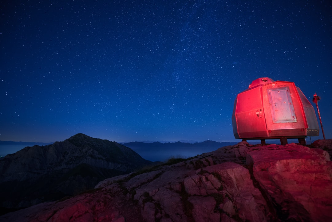 A red light lit bivouac is seen under a starry night on top of Grigna Meridionale mount, Italy.