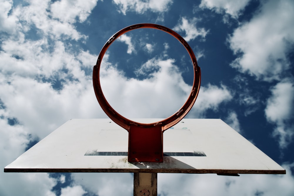 white and red basketball hoop under white clouds and blue sky at daytime