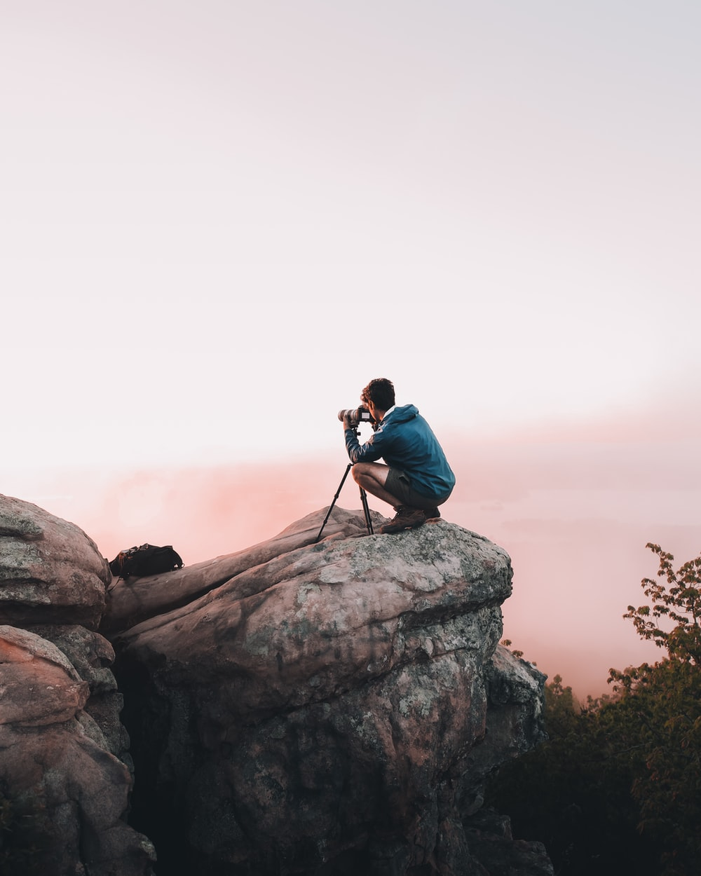 man using telescope white standing on mountain edge