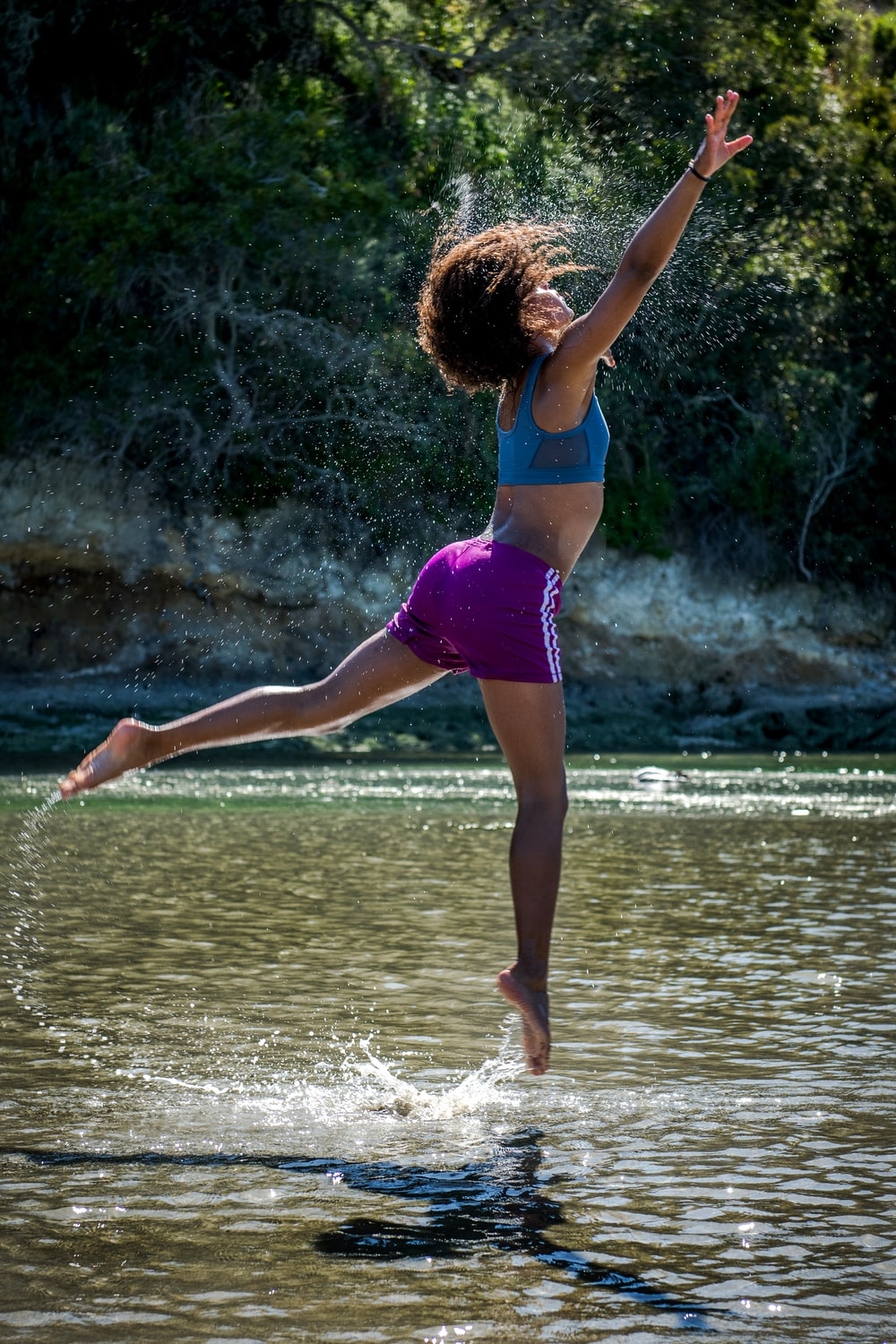 woman jumping on body of water near trees during daytime
