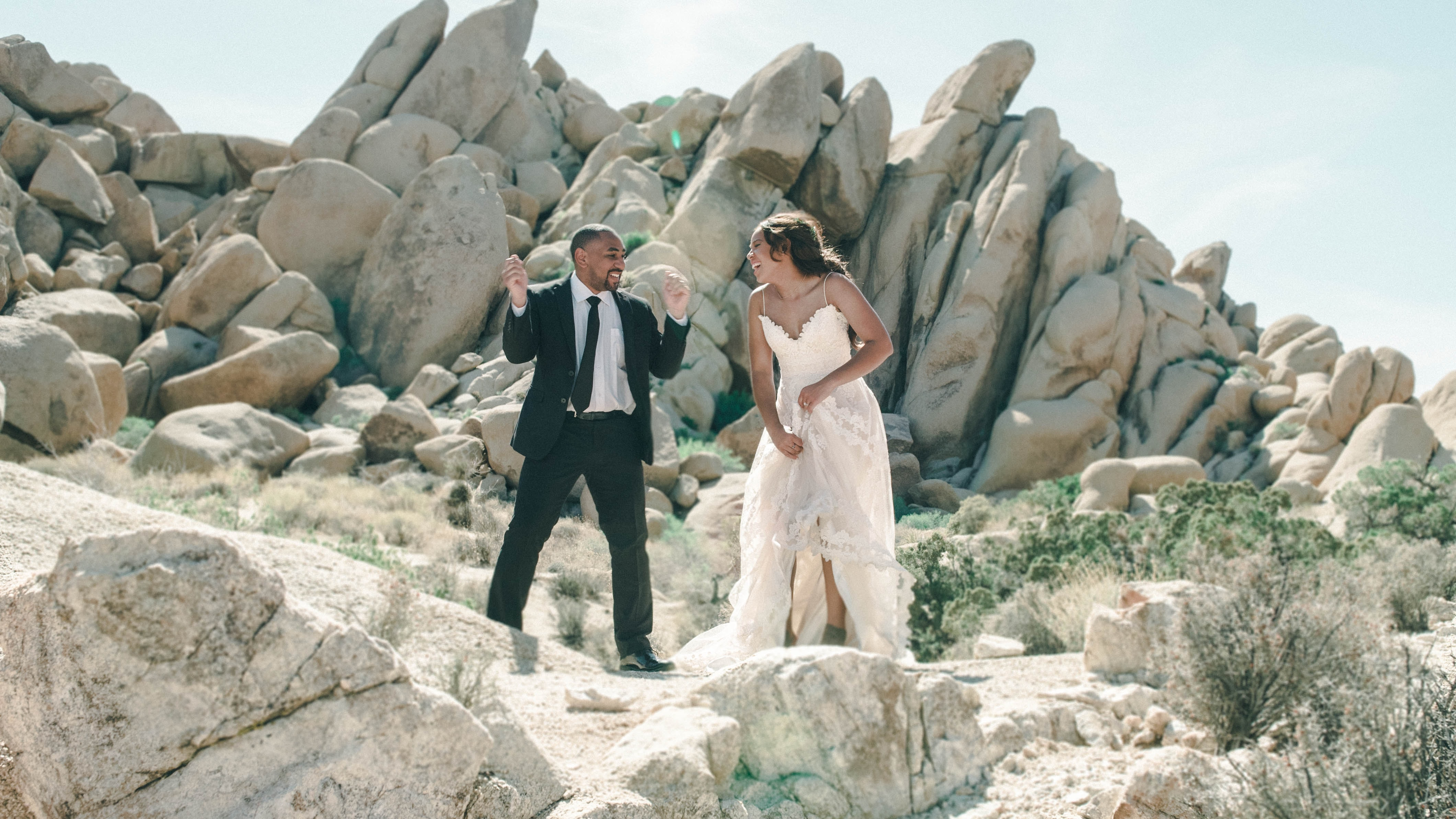 newly couple standing on rocks outside