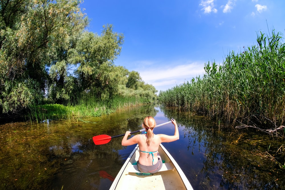 woman riding boat holding paddle