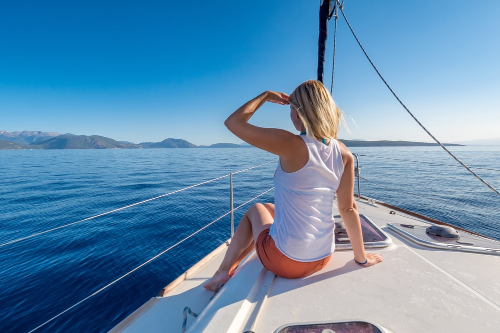 woman sitting on yacht looking mountain