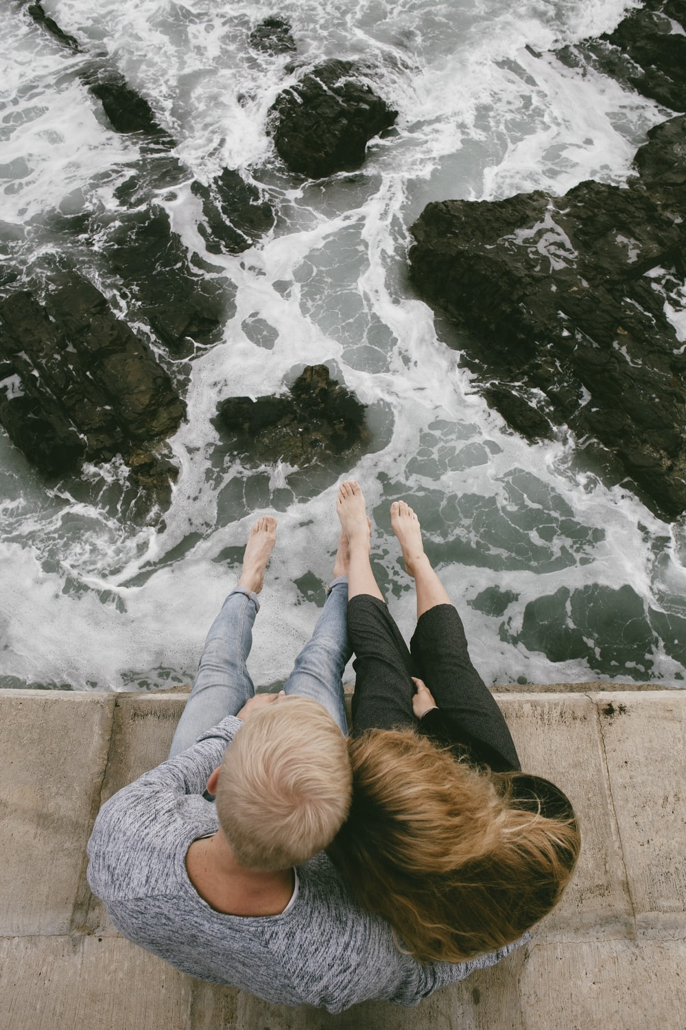 man and woman sitting on cliff near body of water