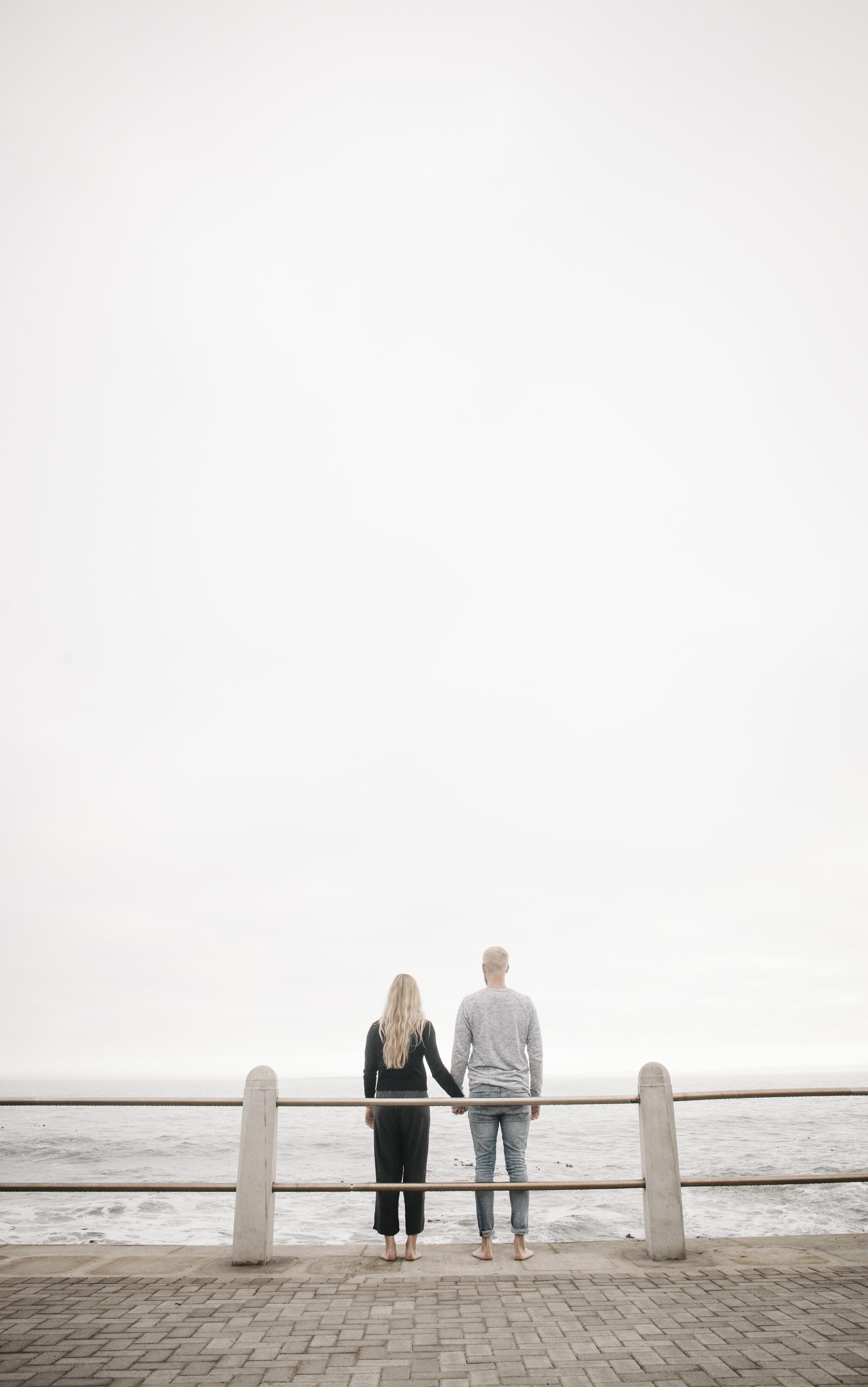 couple leaning on guard rail while holdings hands facing ocean at daytime