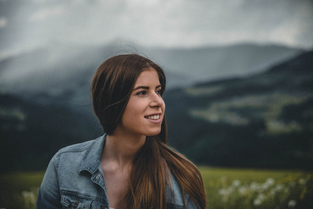 woman in denim jacket and mountain at distance