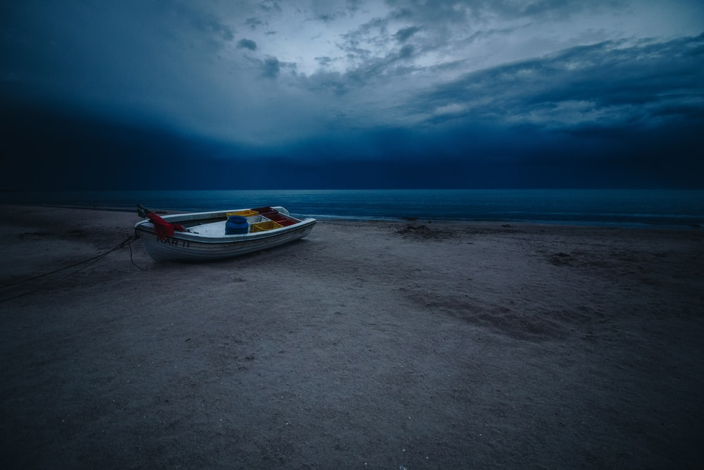rule of thirds photography of white boat on seashore