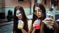 two women taking selfie while sipping straws
