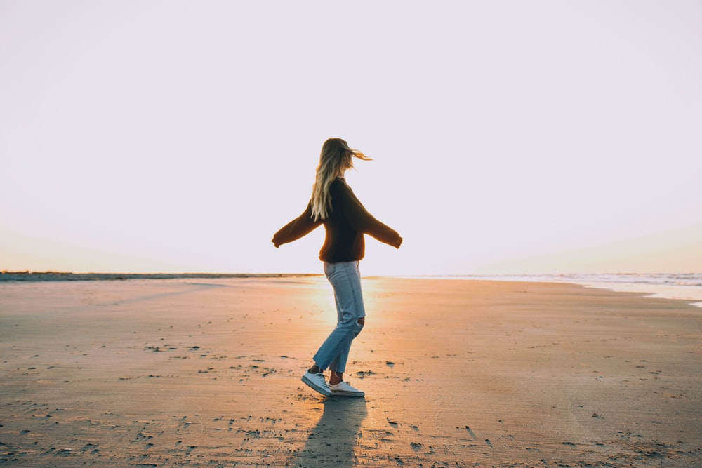 woman standing on sand near seashore during golden hour