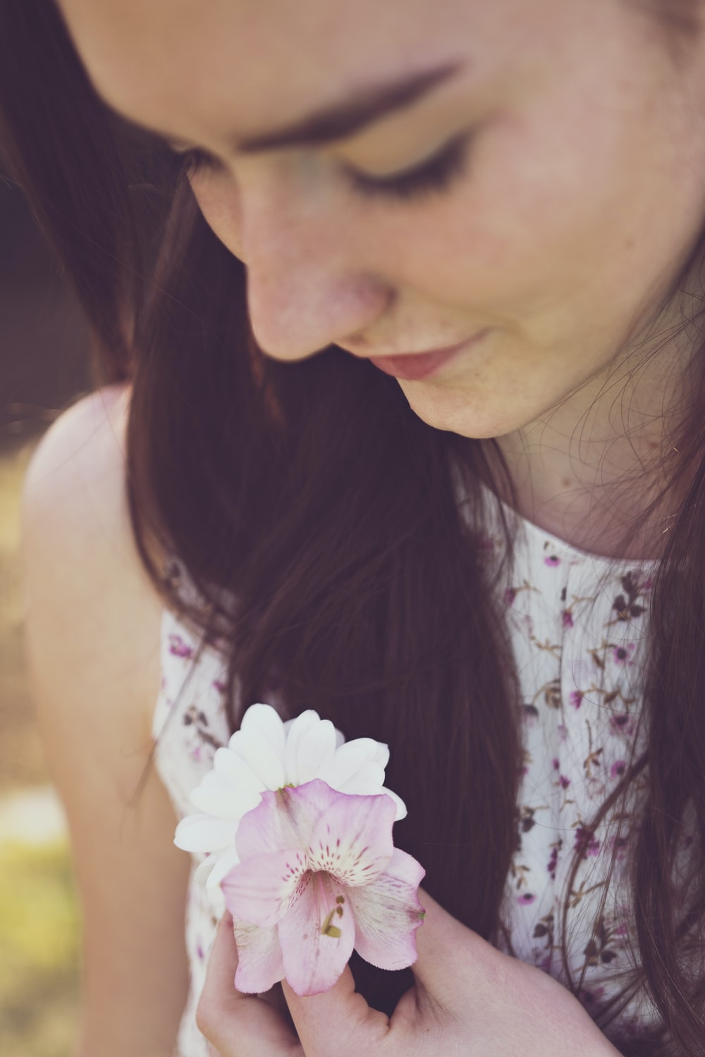 woman holding white and purple orchids