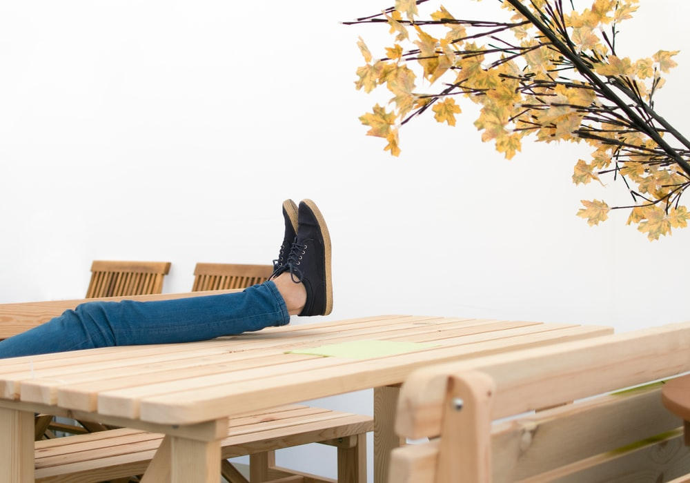 woman resting on plank picnic table