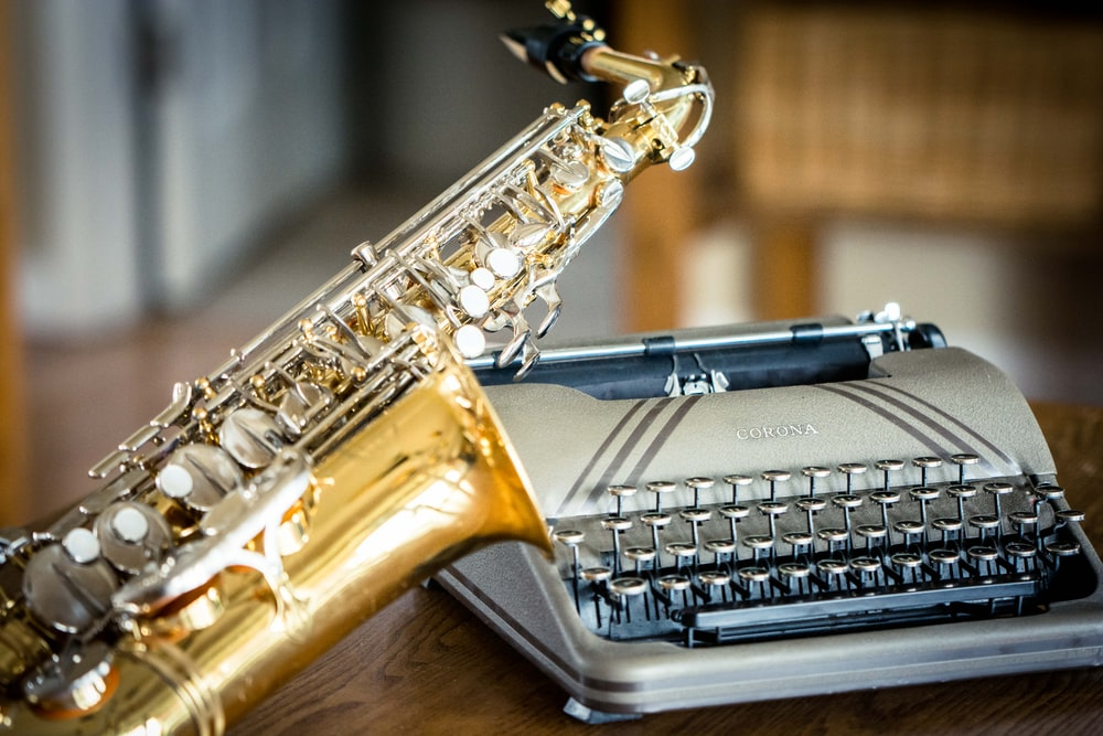 brass saxophone and typewriter on table