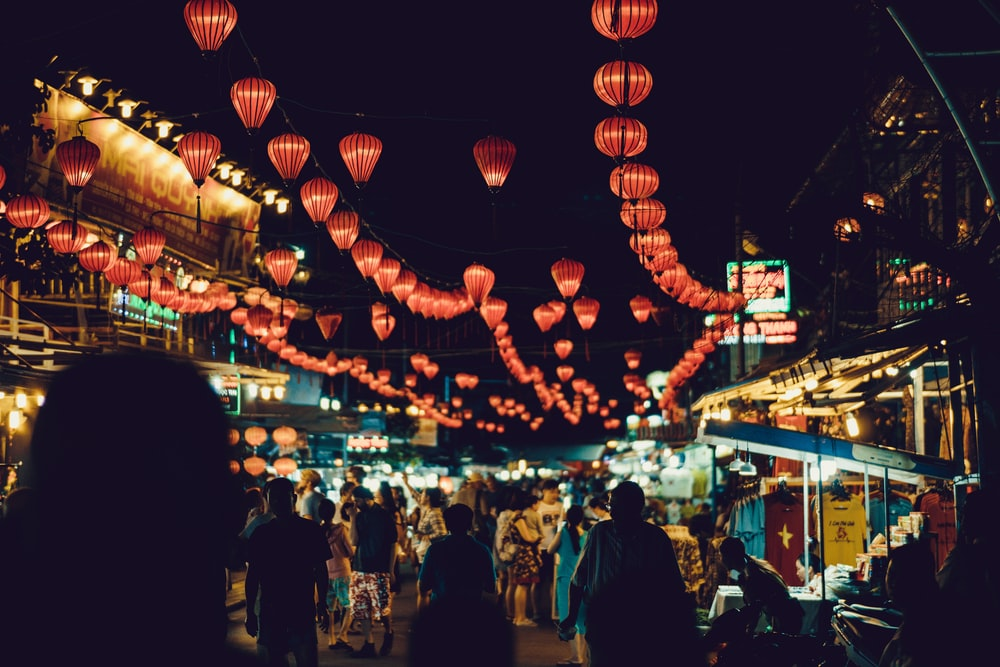 people walking between food stalls under chinese lanterns