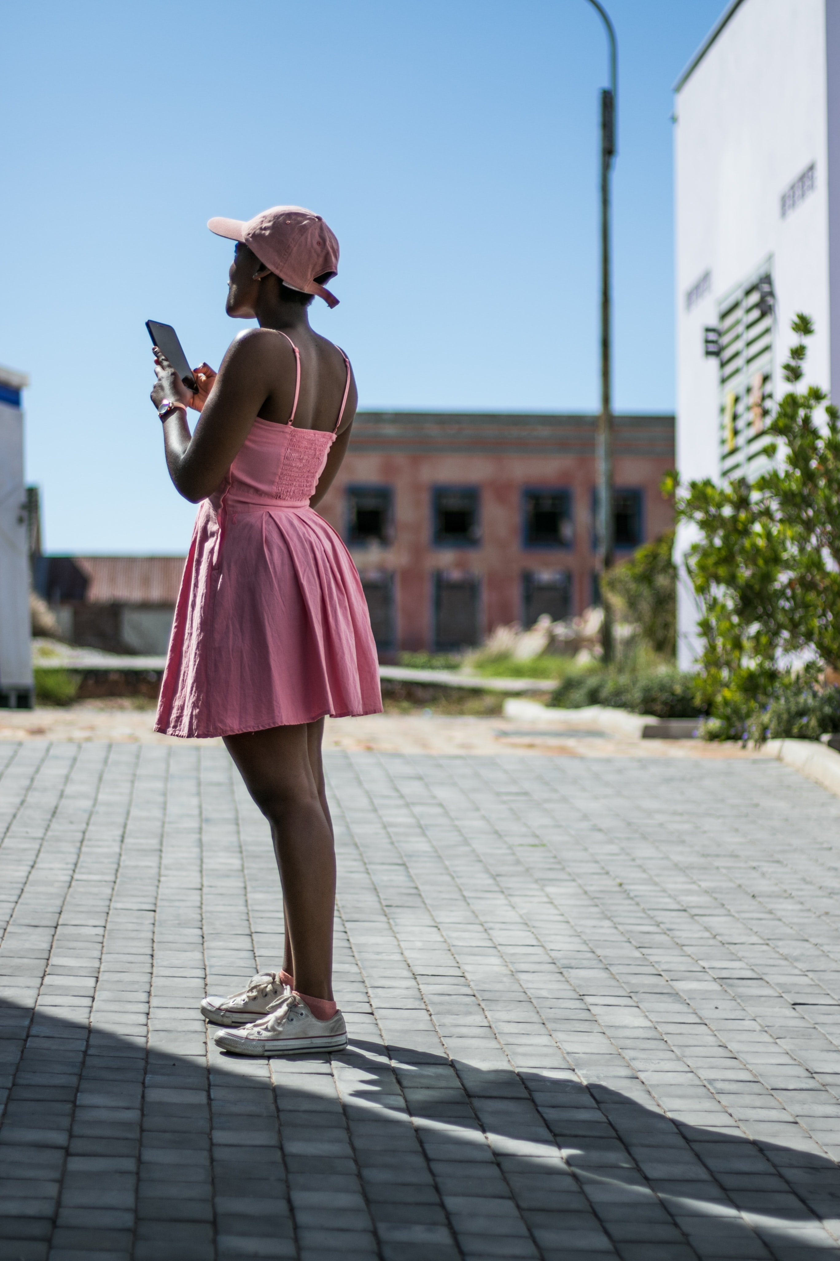 woman in pink spaghetti-strap mini dress using smartphone