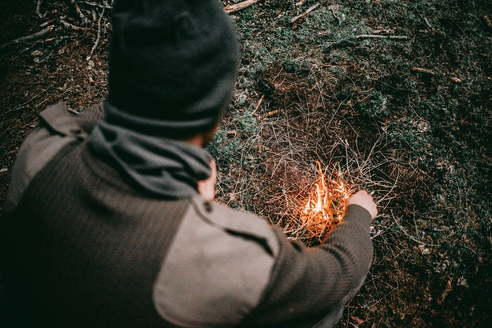 man making fire with grass