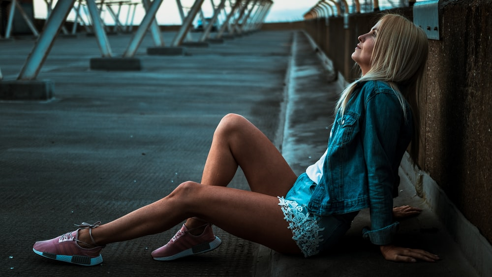 woman looking upward while resting down on road