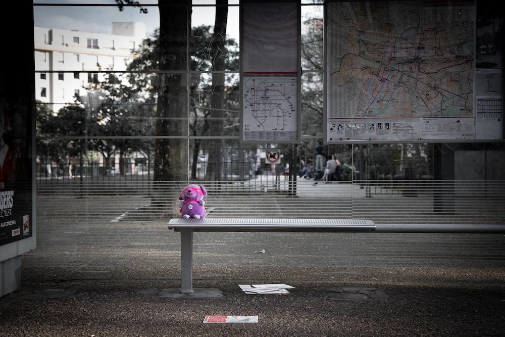 purple animal plush toy on gray metal bench beside street during daytime