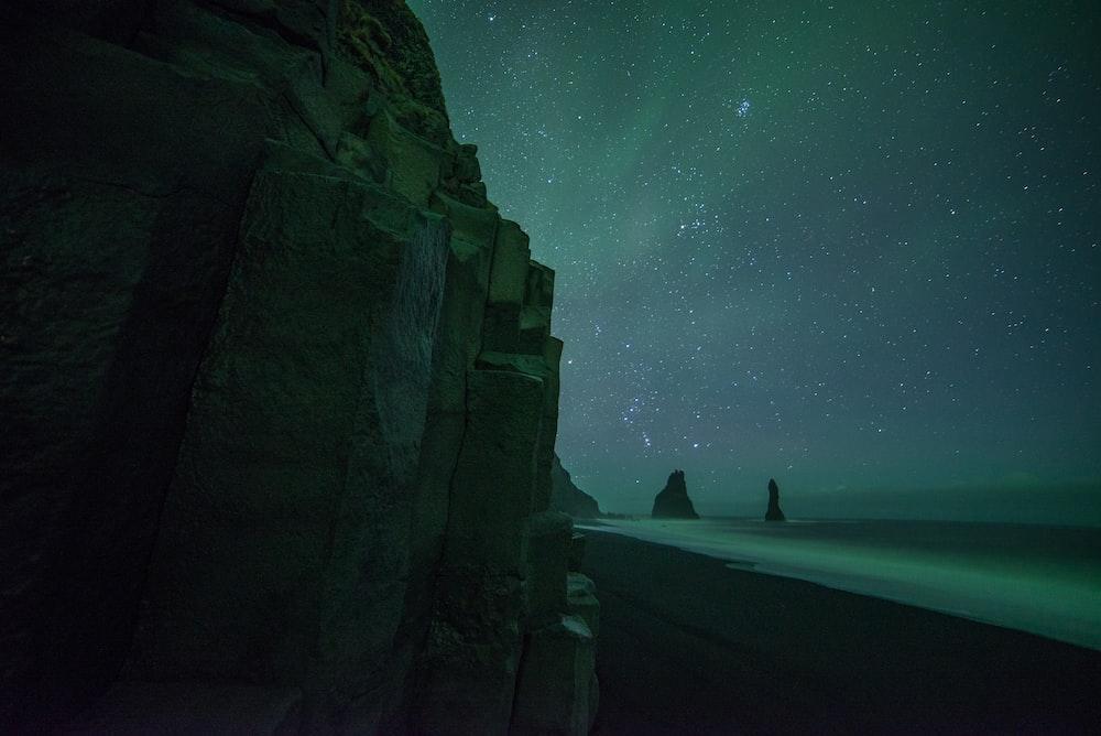 brown rocky mountain under green aurora borealis