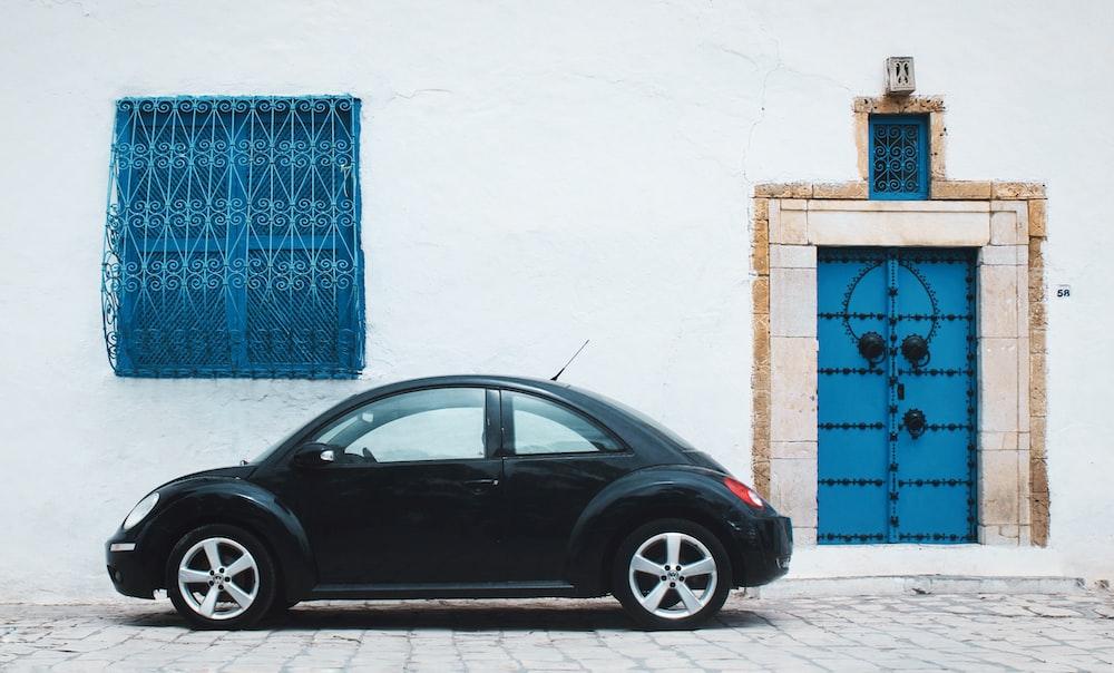 black beetle car near house