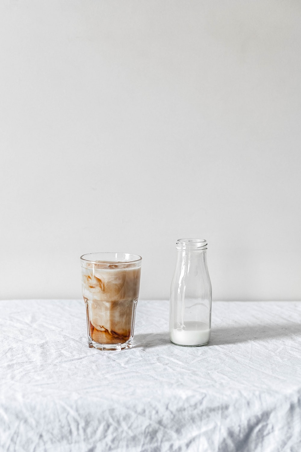 white beverage filled clear glass bottle beside brown liquid filled clear pint glass