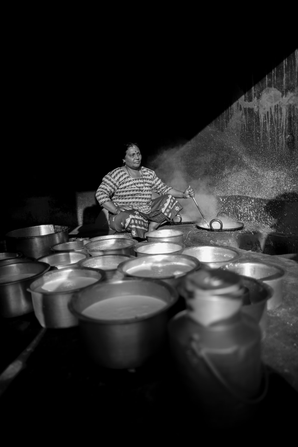 grayscale photography of woman cooking while holding a ladle