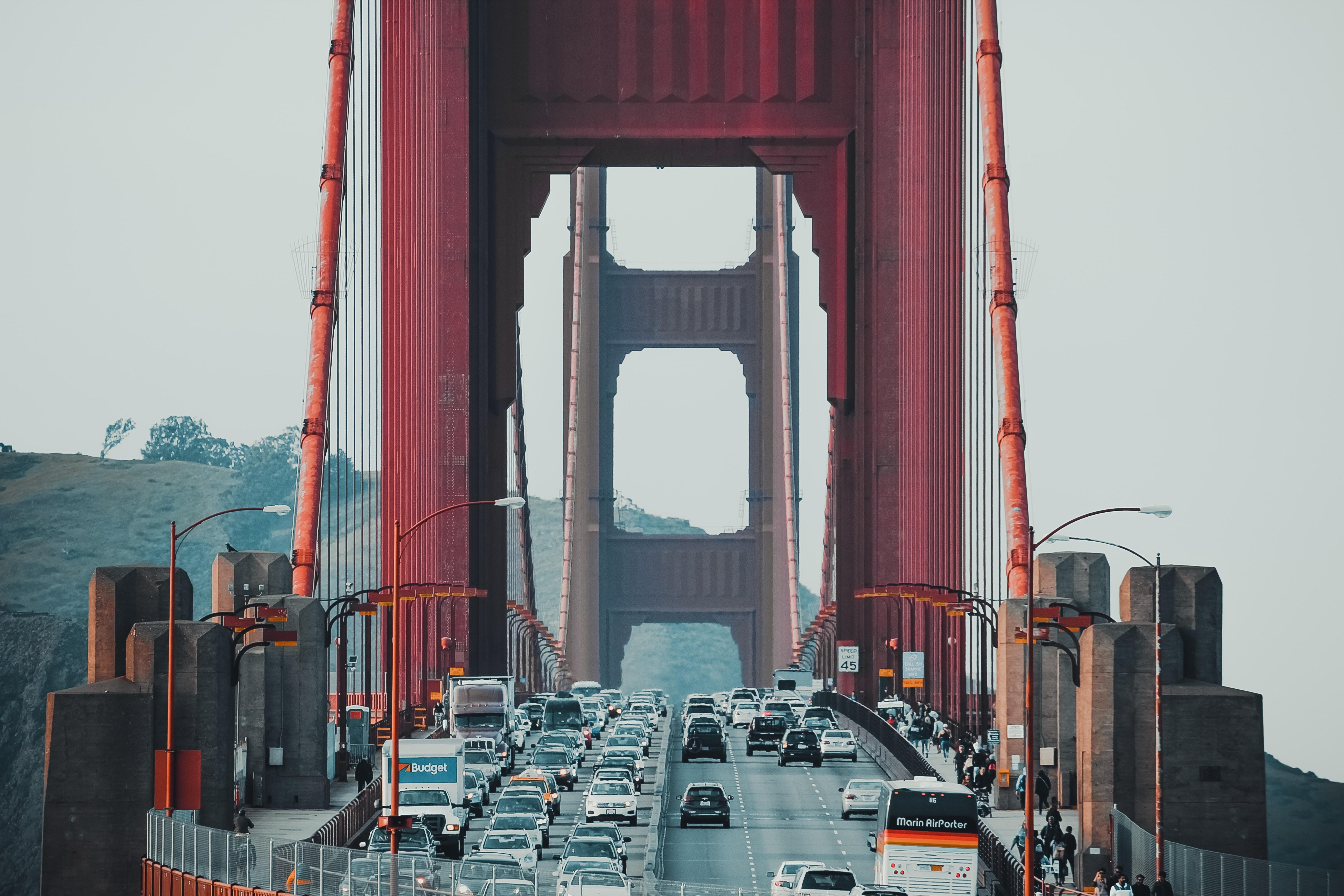 vehicles crossing Golden Gate Bridge at daytime