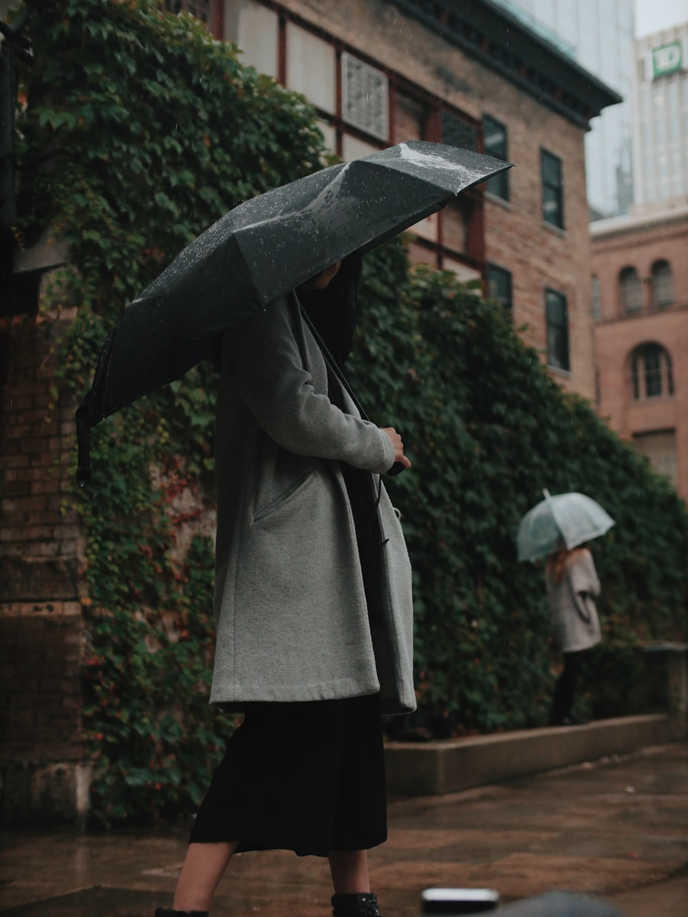 woman in gray coat holding black umbrella