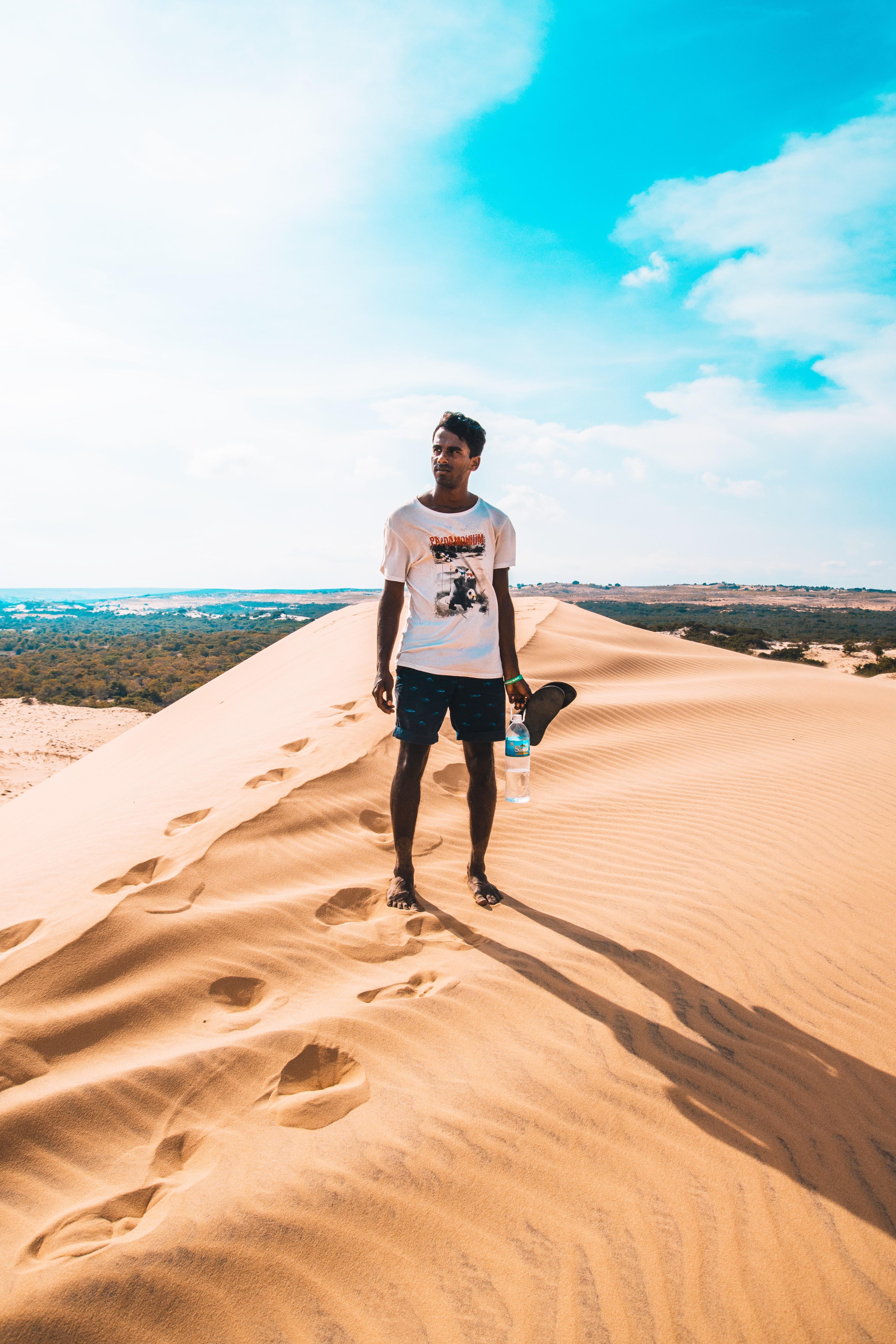 man standing on desert mountain