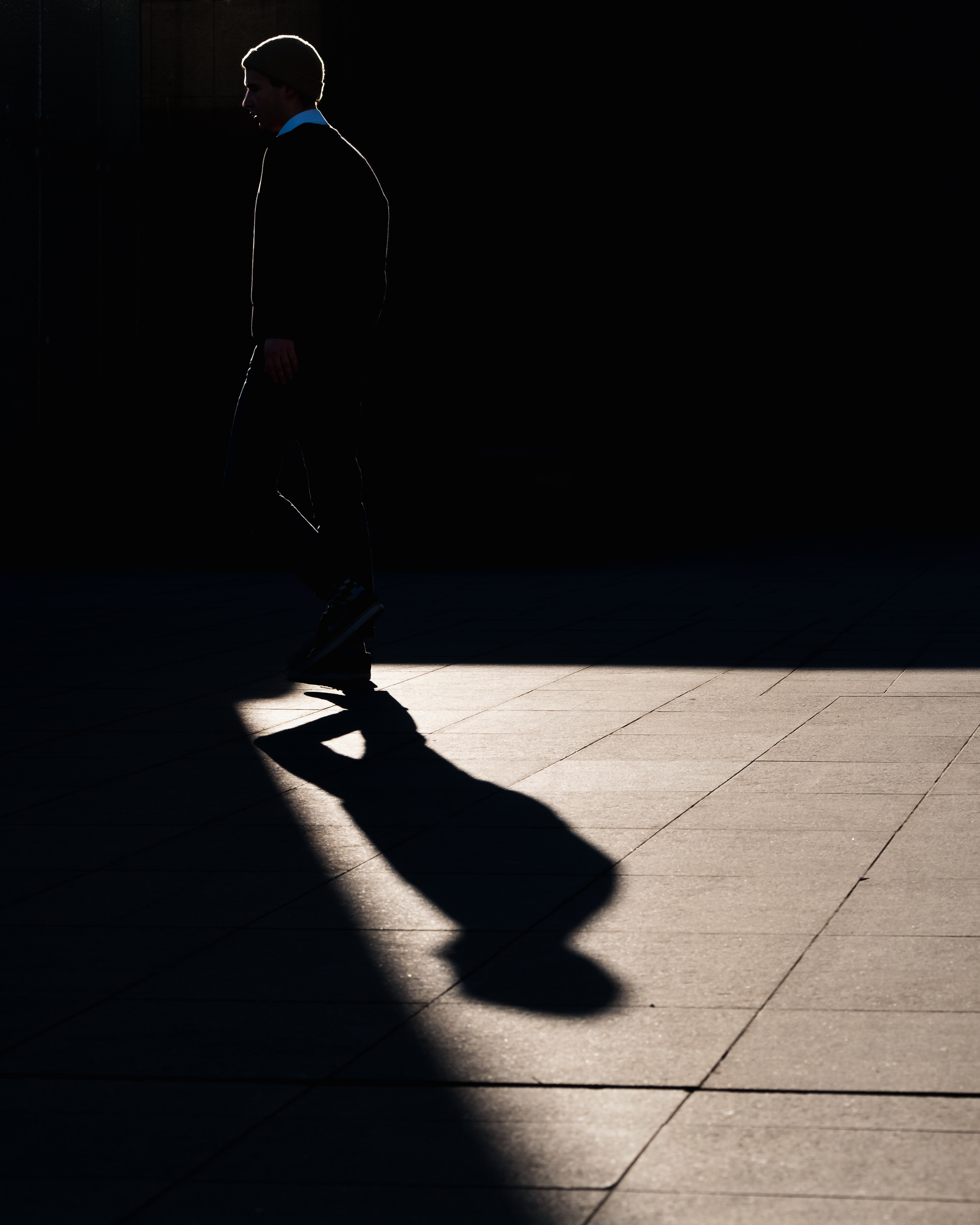 silhouette of man walking on pavement