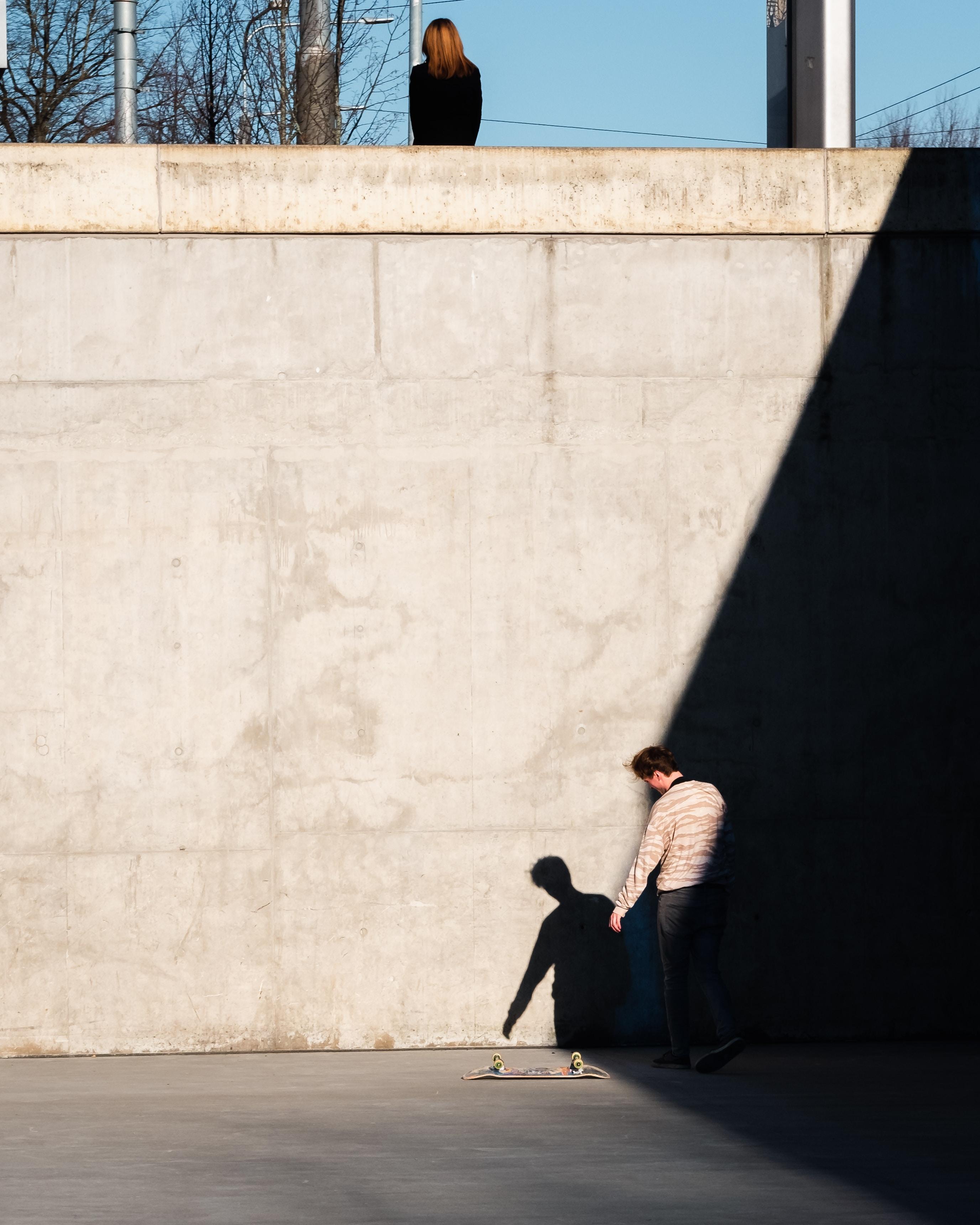 man standing beside skateboard