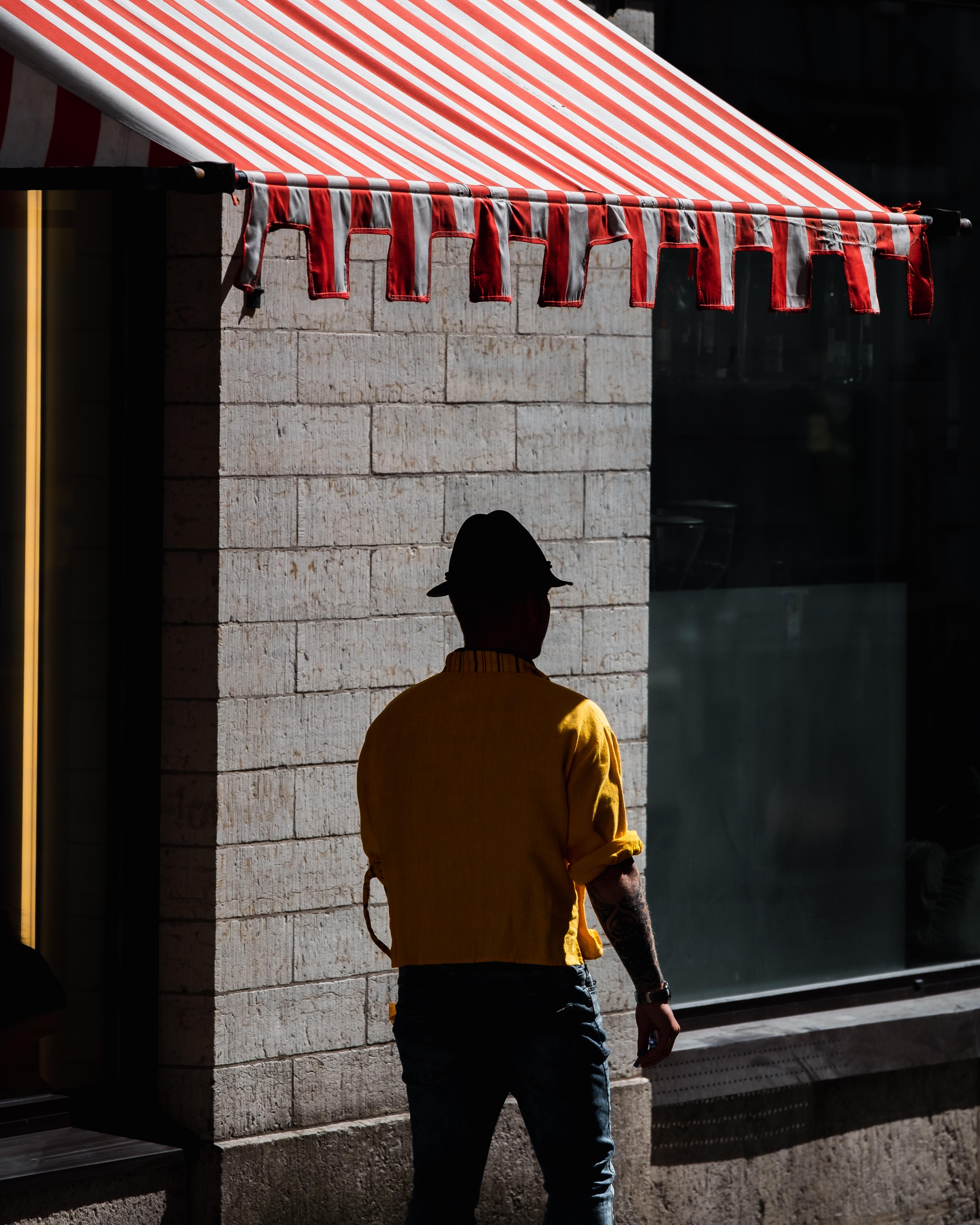 man walking under red and white striped awning during daytime