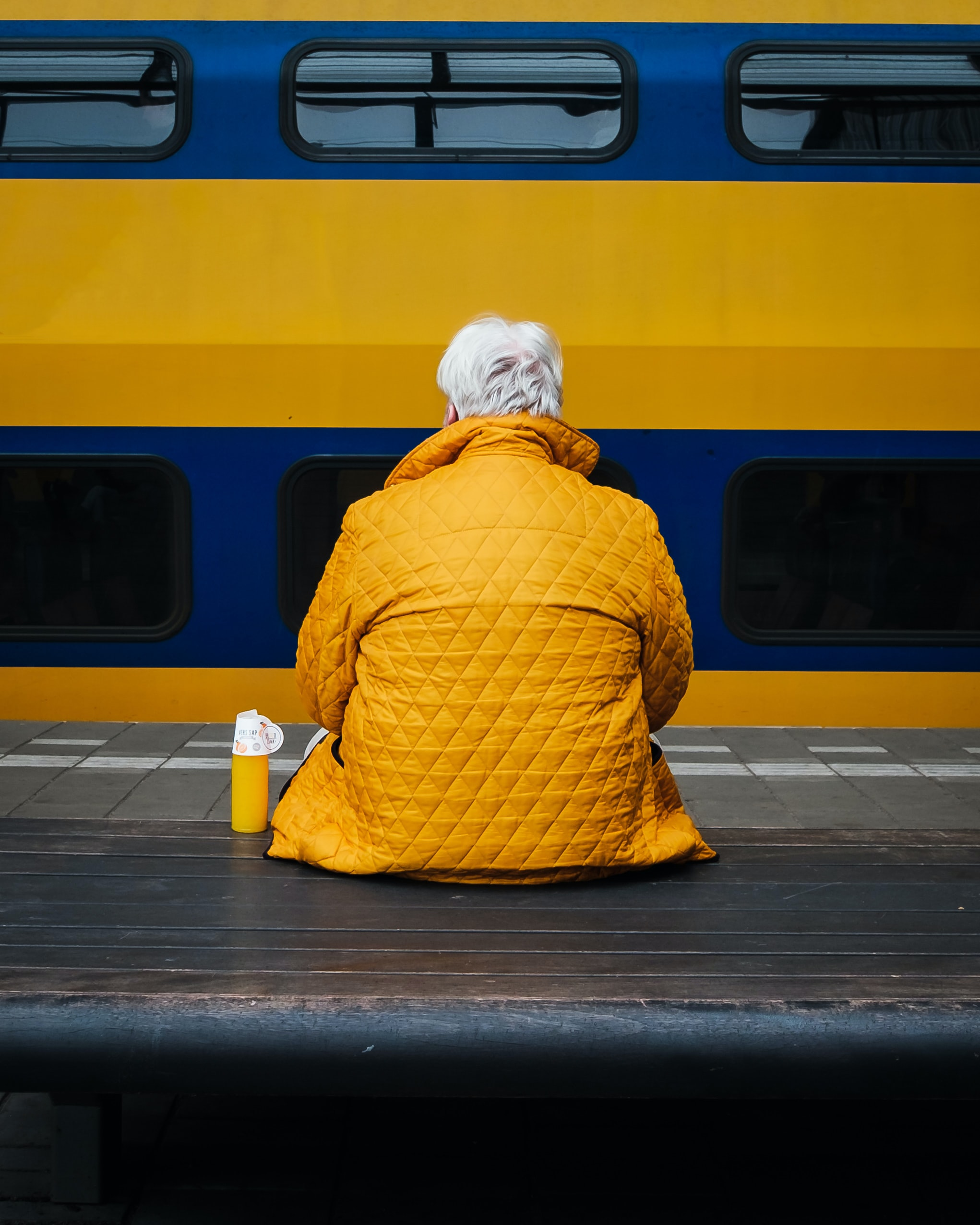 person wearing jacket and sitting on bench