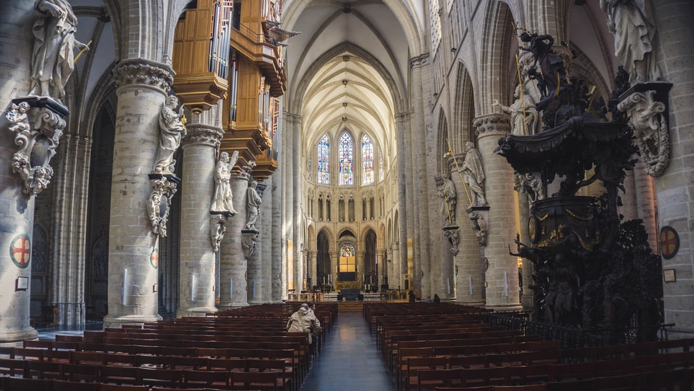 people sitting in pew inside cathedral